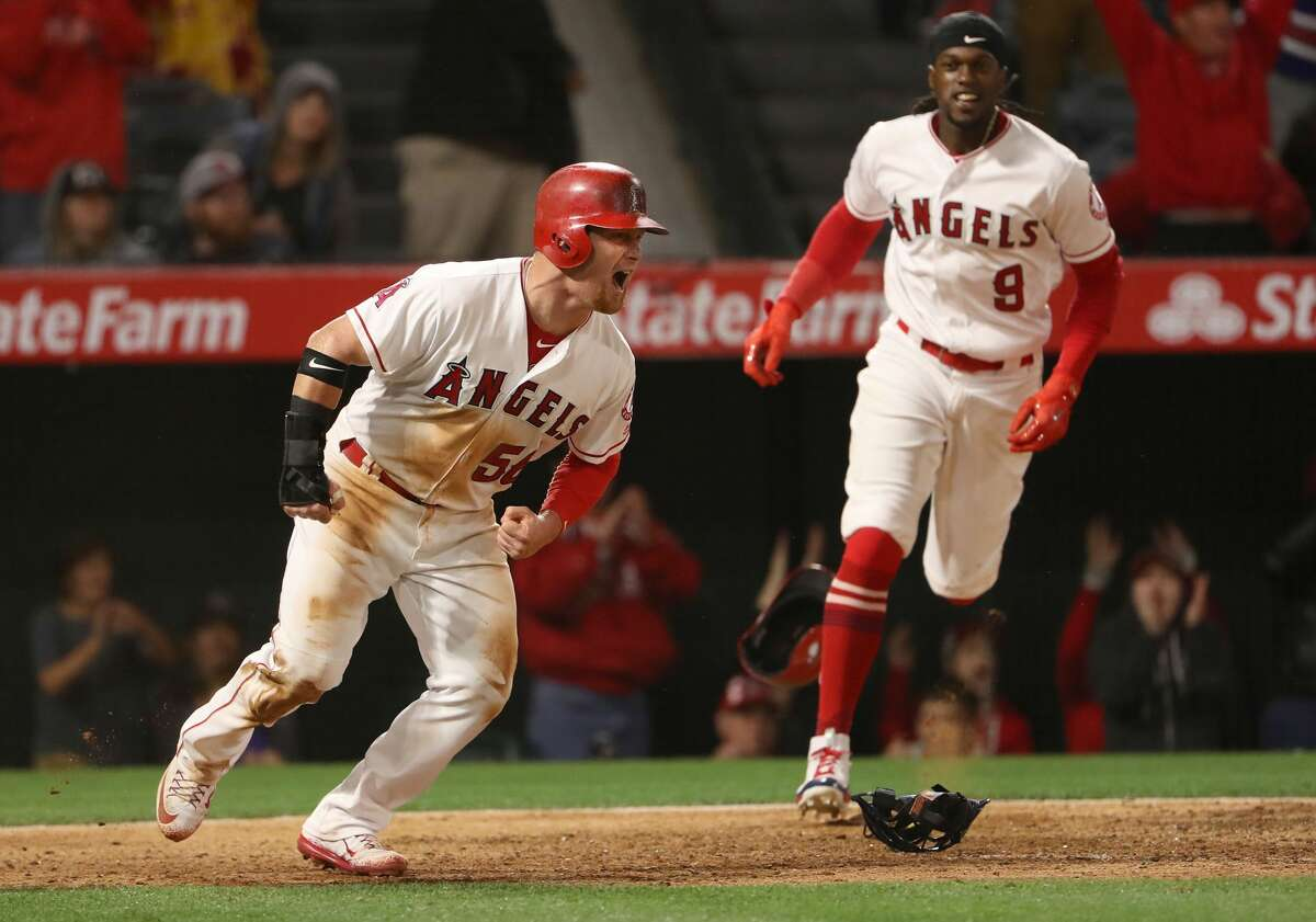 ANAHEIM, CA - MAY 06: Kole Calhoun #56 of the Los Angeles Angels of Anaheim reacts after scoring the game-winning run in the ninth inning on a single by Andrelton Simmons #2 (not in photo) as Cameron Maybin #9 looks to join the celebration after they defeated the Houston Astros -1 in their MLB game at Angel Stadium of Anaheim on May 6, 2017 in Anaheim, California. (Photo by Victor Decolongon/Getty Images)