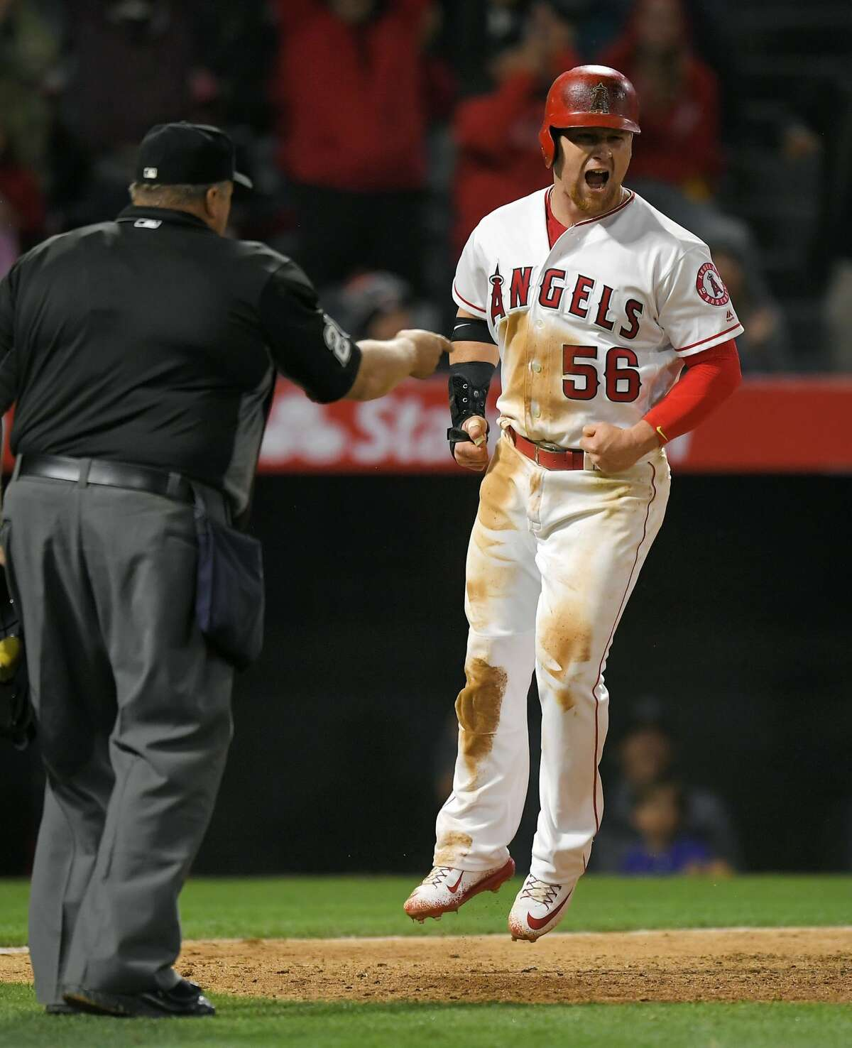 Los Angeles Angels' Kole Calhoun, right, celebrates after scoring the winning run on a single by Andrelton Simmons during the ninth inning of a baseball game against the Houston Astros, Saturday, May 6, 2017, in Anaheim, Calif. The Angels won 2-1. (AP Photo/Mark J. Terrill)