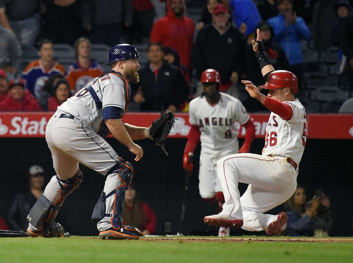Los Angeles Angels' Kole Calhoun, right, scores the winning run on a single by Andrelton Simmons as Houston Astros catcher Brian McCann takes a late throw during the ninth inning of a baseball game against the Houston Astros, Saturday, May 6, 2017, in Anaheim, Calif. The Angels won 2-1. (AP Photo/Mark J. Terrill)
