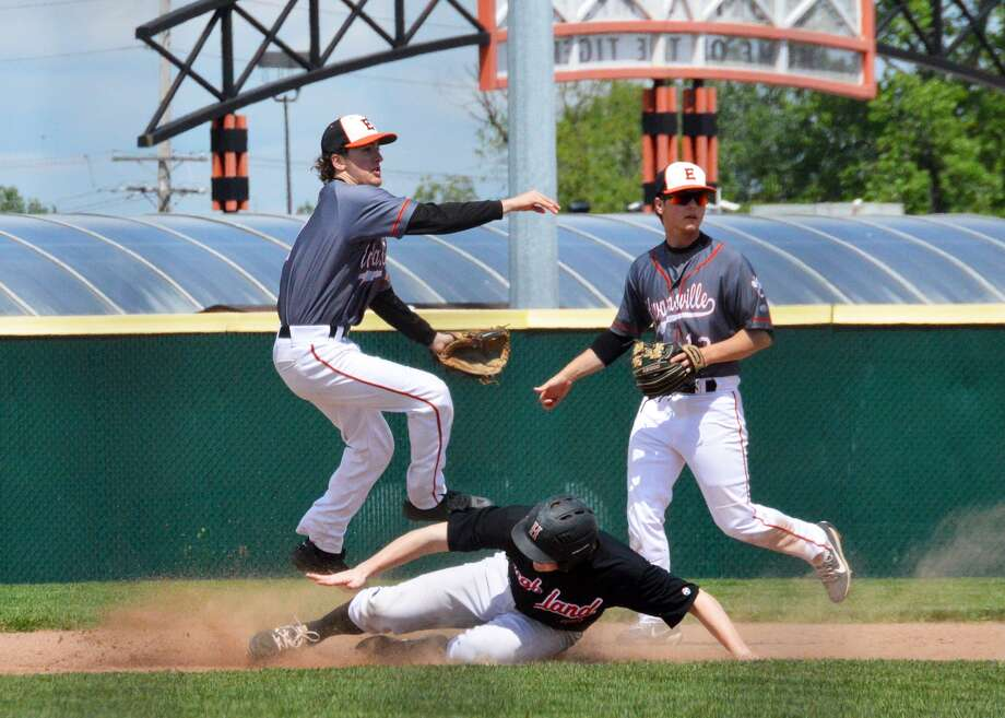 Edwardsville shortstop Kade Burns, left, leaps over a Highland runner as he tries to complete a double play during Saturday's game at Tom Pile Field. Second baseman Joel Quirin, right, is backing up the play.