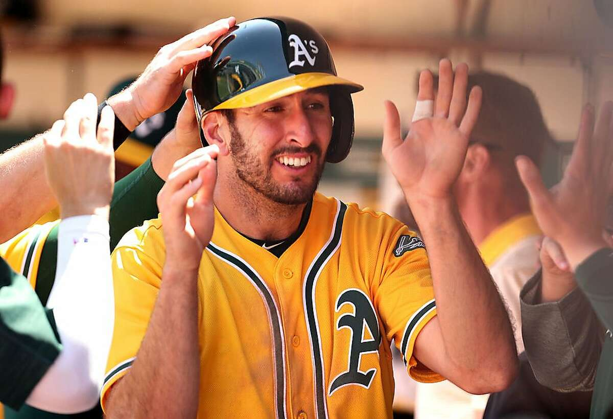 Oakland Athletics' Adam Rosales is welcomed back to the dugout after scoring on Rajai Davis' double in 3rd inning against Detroit Tigers during MLB game at Oakland Coliseum in Oakland, Calif., on Sunday, May 7, 2017.