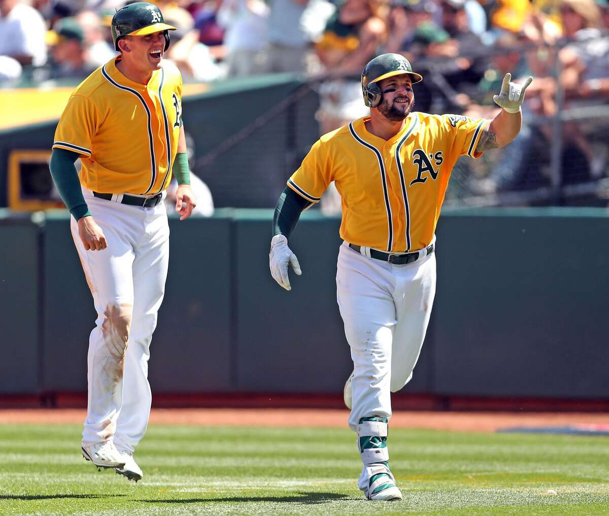 Oakland Athletics' Yonder Alonso and Ryon Healy react to Alonso's 2-run home run in 4th inning against Detroit Tigers during MLB game at Oakland Coliseum in Oakland, Calif., on Sunday, May 7, 2017.