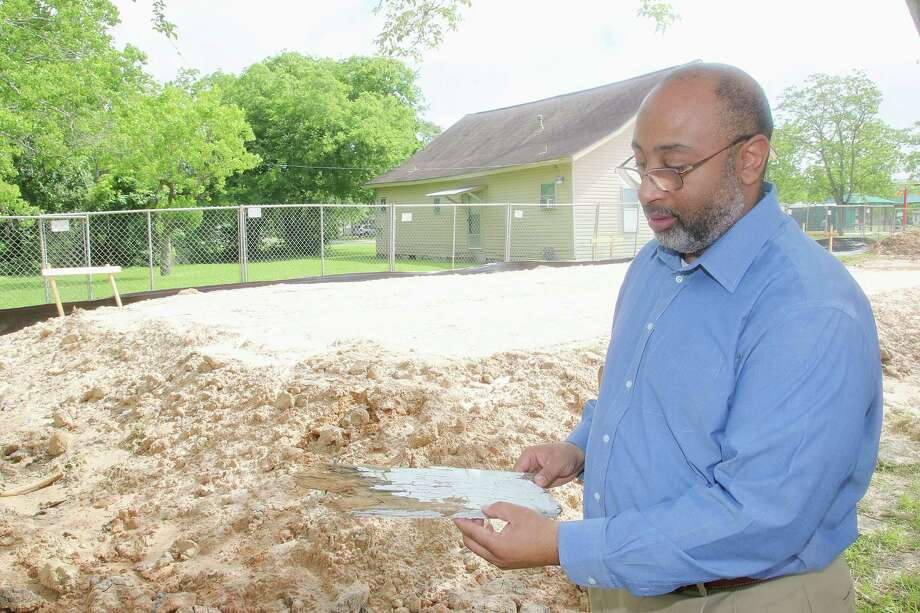 "La Porte City Manager Corby Alexander holds a piece of wood from the La Porte Colored School, a one-room schoolhouse that housed the city's black students until the early 1950s. He stands on the site where a replica of the building will be built. ""The community is very, very eager to see the work,"" he says. Photo: Pin Lim, Freelance / Copyright Forest Photography, 2017."