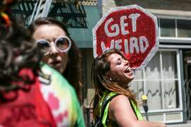 A girl dances at with a sign at the 18th annual How Weird Street Faire on Sunday, May 6, 2017 in San Francisco, Calif.