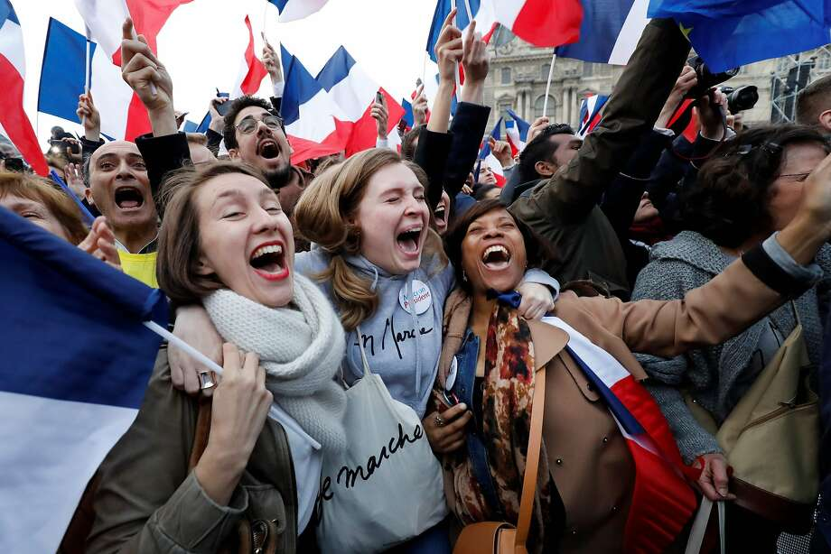Supporters of French president-elect Emmanuel Macron react at the Louvre Museum in Paris on May 7, 2017, after the second round of the French presidential election. Emmanuel Macron was elected French president on May 7, 2017 in a resounding victory over far-right Front National (FN - National Front) rival after a deeply divisive campaign. / AFP PHOTO / Patrick KOVARIKPATRICK KOVARIK/AFP/Getty Images Photo: PATRICK KOVARIK, AFP/Getty Images