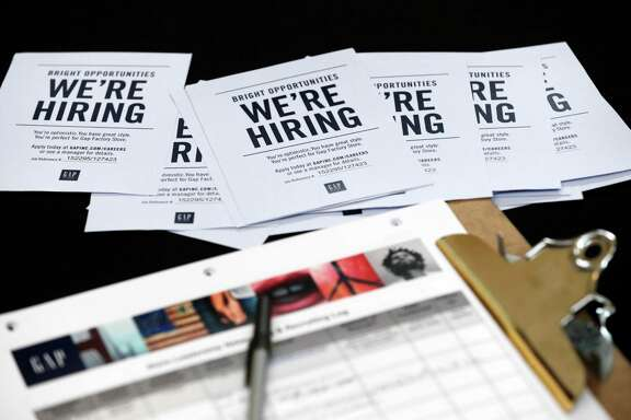 Job applications sit on a table during a job fair. The five fastest-growing sectors in the last 12 months have been: temporary help, professional and technical services, construction, education and health care.