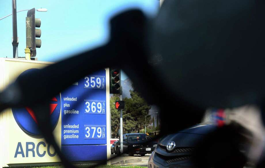 A gas station's display of prices per gallon is seen behind a gas pump filling the tank of a vehicle in Alhambra, California on November 6, 2013. The average price for a gallon of self-serve regular gasoline dropped to its lowest amount since January 10  in Los Angeles County today, falling eight-tenths of a cent to 3.68 USD. The ongoing decreases in gas prices are the result of lower wholesale prices and last Friday's shift to a winter blend of gasoline, which costs less to produce, according to the Automobile Club of Southern California. AFP PHOTO/Frederic J. BROWN        (Photo credit should read FREDERIC J. BROWN/AFP/Getty Images) Photo: FREDERIC J. BROWN / AFP/Getty Images / 2013 AFP