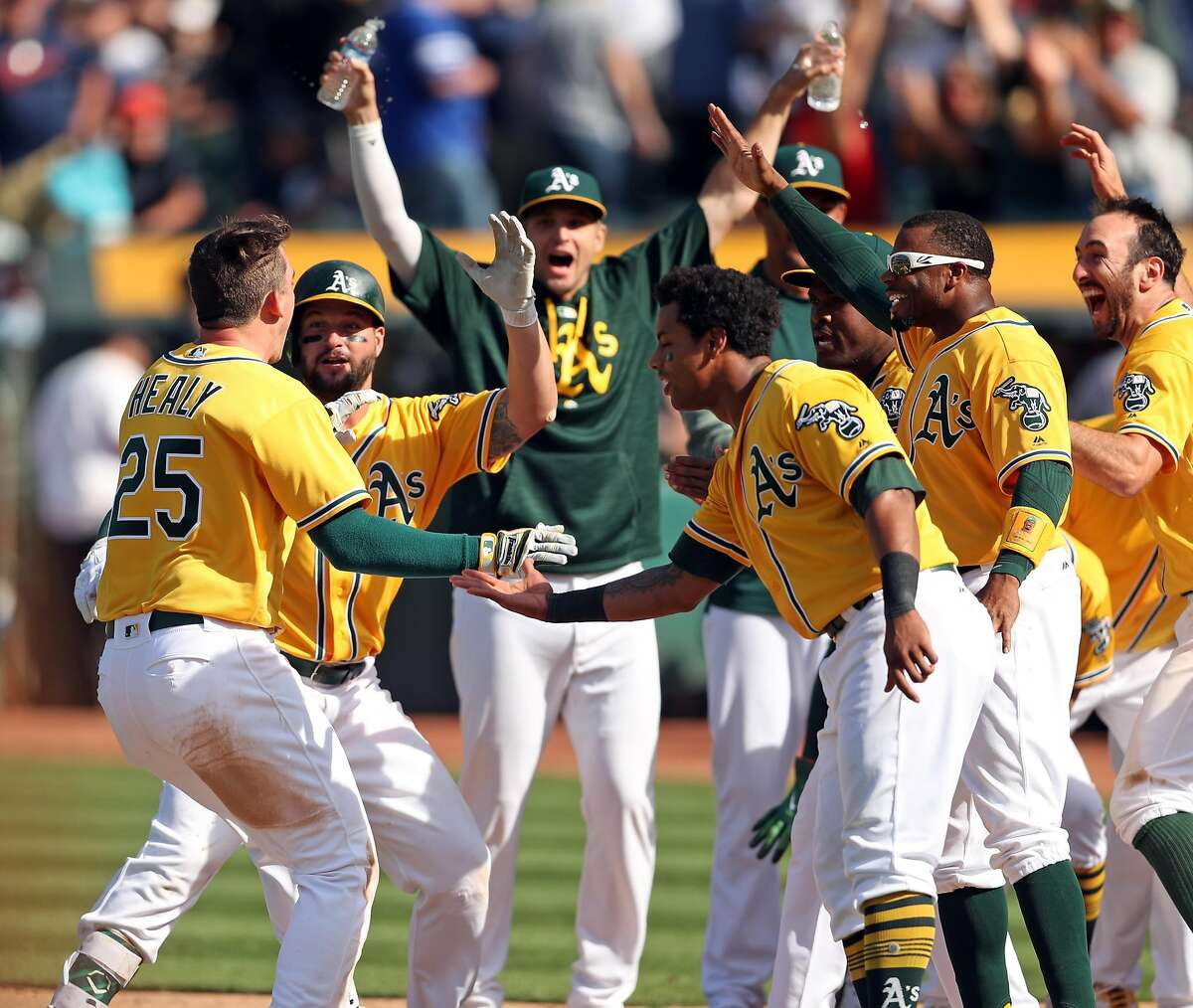 Oakland Athletics' Ryon Healy is met at home plate after hitting a 2-run home run giving A's an 8-6 win over Detroit Tigers in MLB game at Oakland Coliseum in Oakland, Calif., on Sunday, May 7, 2017.