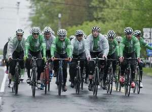 Team 26 cyclists make their way along Main Street in Newtown as they return from Washington DC. Sunday, May 7, 2017