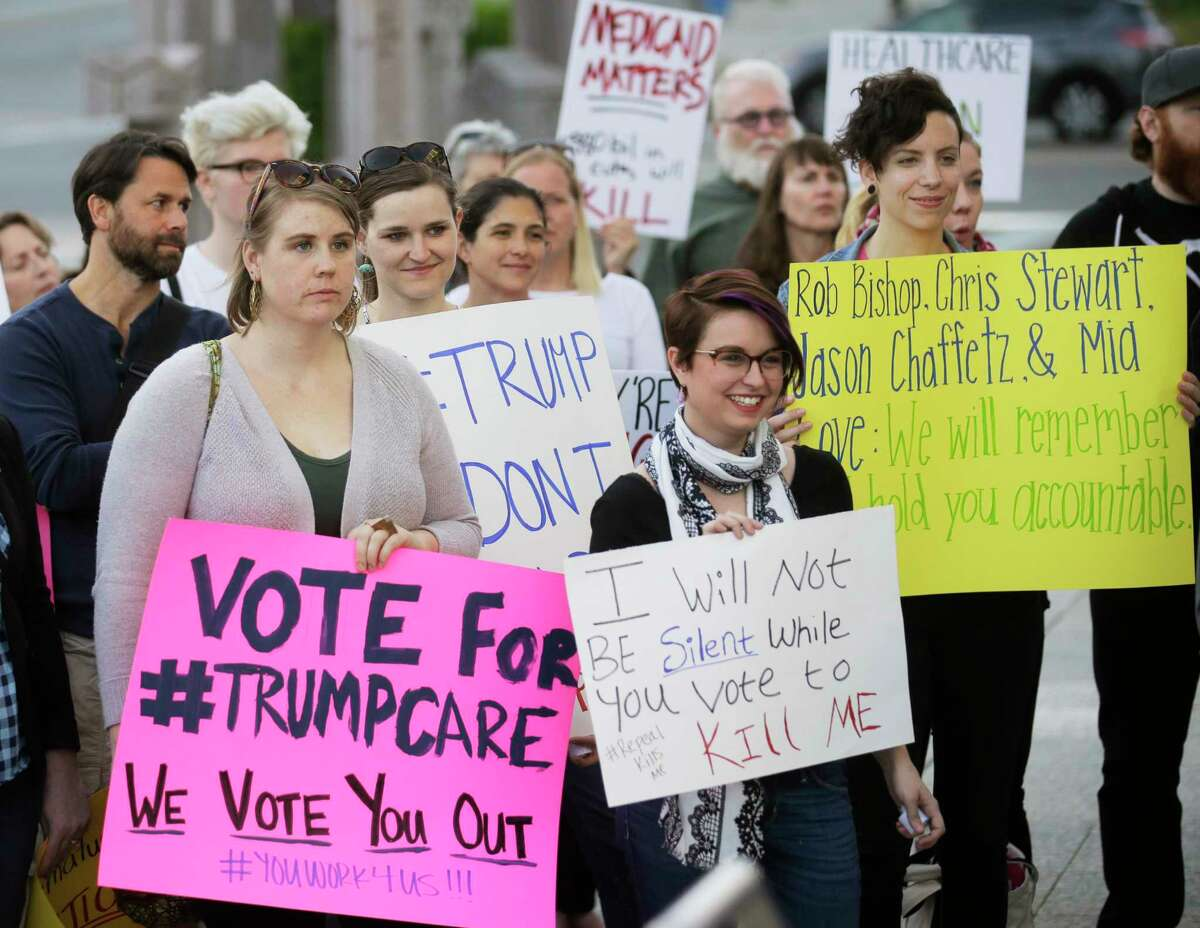 FILE - In this Thursday, May 4, 2017 file photo, demonstrators hold signs during a healthcare rally in Salt Lake City. Utah's all-Republican House delegation voted Thursday in favor of a health care overhaul that could impact people with pre-existing conditions, triggering serious worries from people who fit that category. (AP Photo/Rick Bowmer) ORG XMIT: NY595