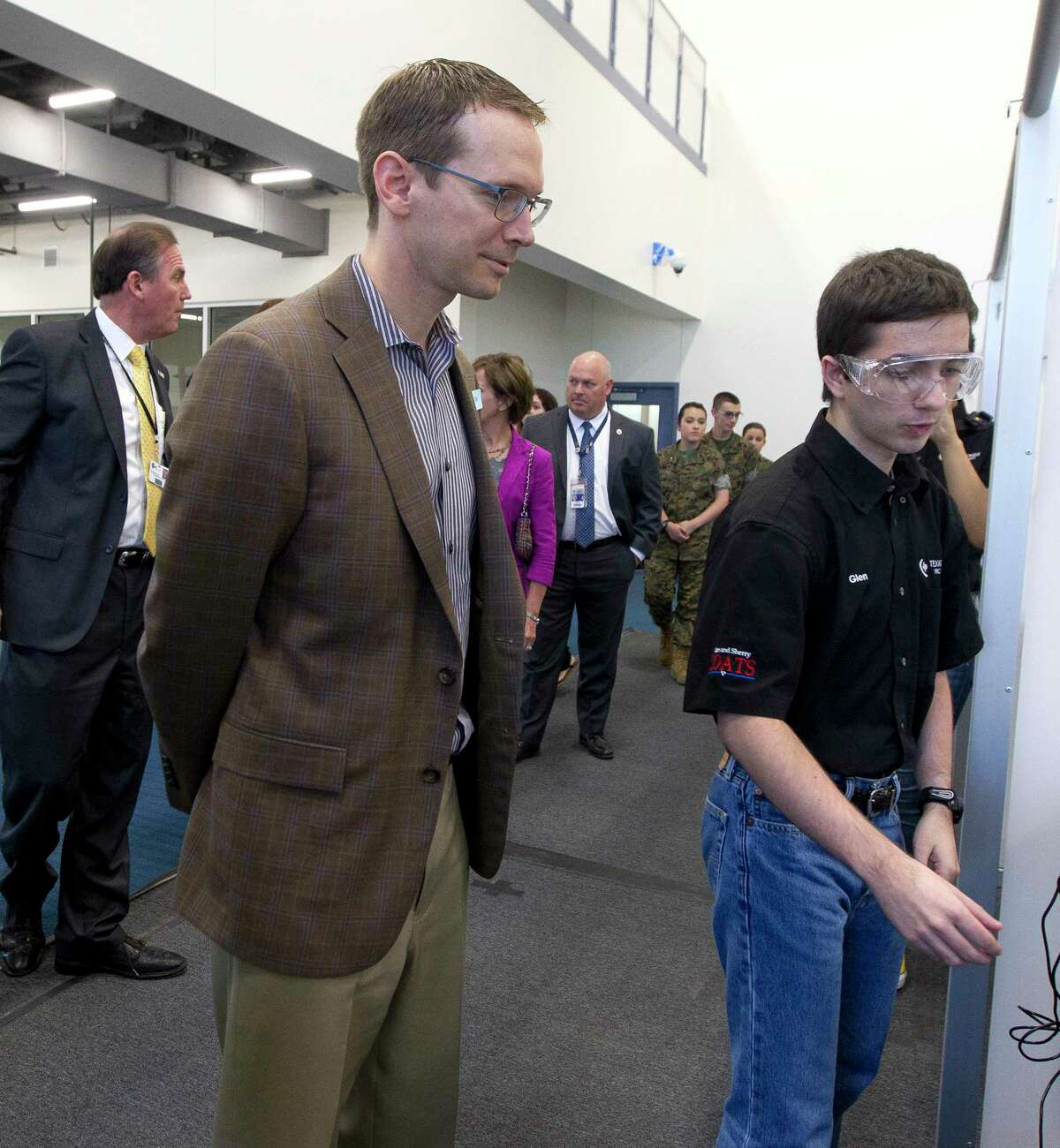 Texas Commissioner of Education Mike Morath, left, receives instructions from Glen Lauratsen on how to control a robot built by student from Conroe ISD Academy of Science and Technology during a tour of College Park High School, Thursday, May 4, 2017, in The Woodlands.