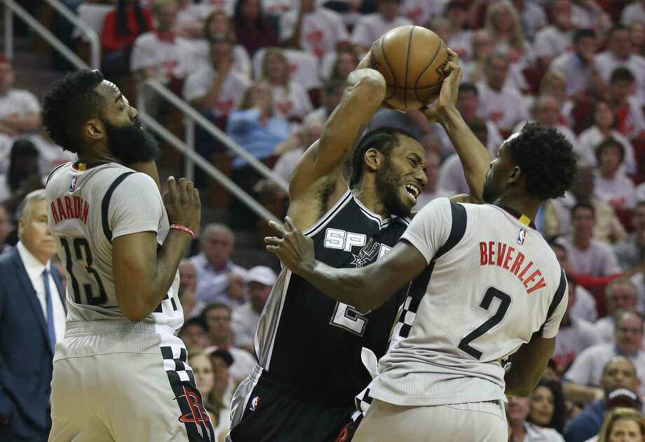 Spurs' Kawhi Leonard is double-teamed by the Rockets' James Harden (13) and Patrick Beverley (2) in Game 4 on May 7, 2017. Photo: Kin Man Hui /San Antonio Express-News / ©2017 San Antonio Express-News