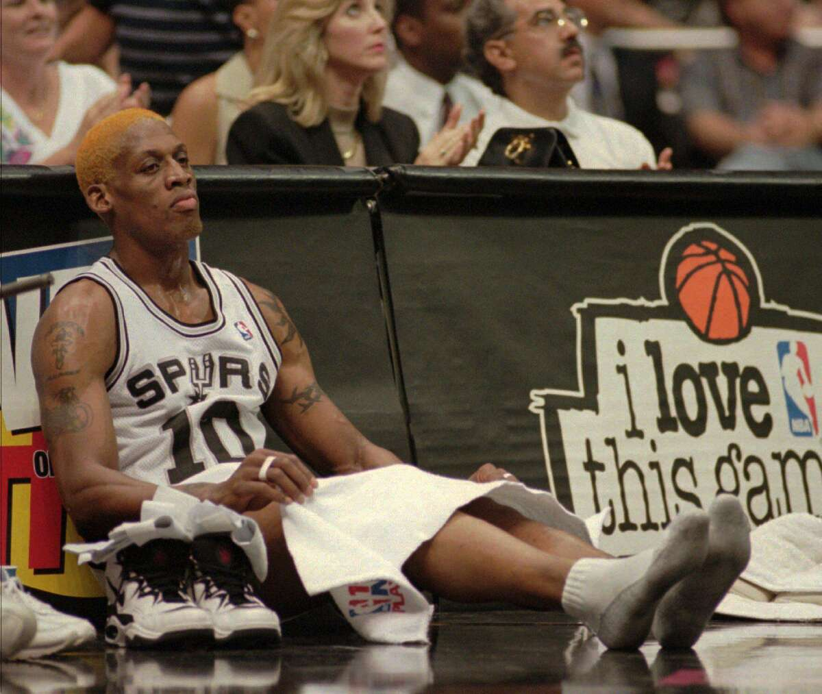 San Antonio Spurs Dennis Rodman sits with shoes off by the bench against the Houston Rockets in the second game of the Western Conference Finals Wednesday, May 24, 1995 in San Antonio. (AP Photo/David J. Phillip)