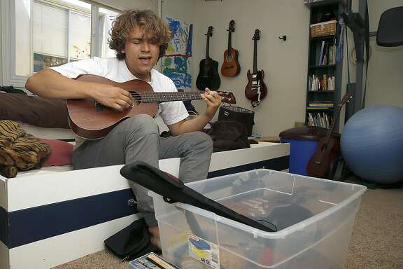 Sage Spencer, 17, plays ukulele in his room while he packs his belongings to pursue teaching and acting in Los Angeles on Friday, May 5, 2017, in San Francisco, Calif.   Starting college at age 13, he graduated to be a substitute teacher.  After applying and doing all the requirements, Sage experienced age discrimination.