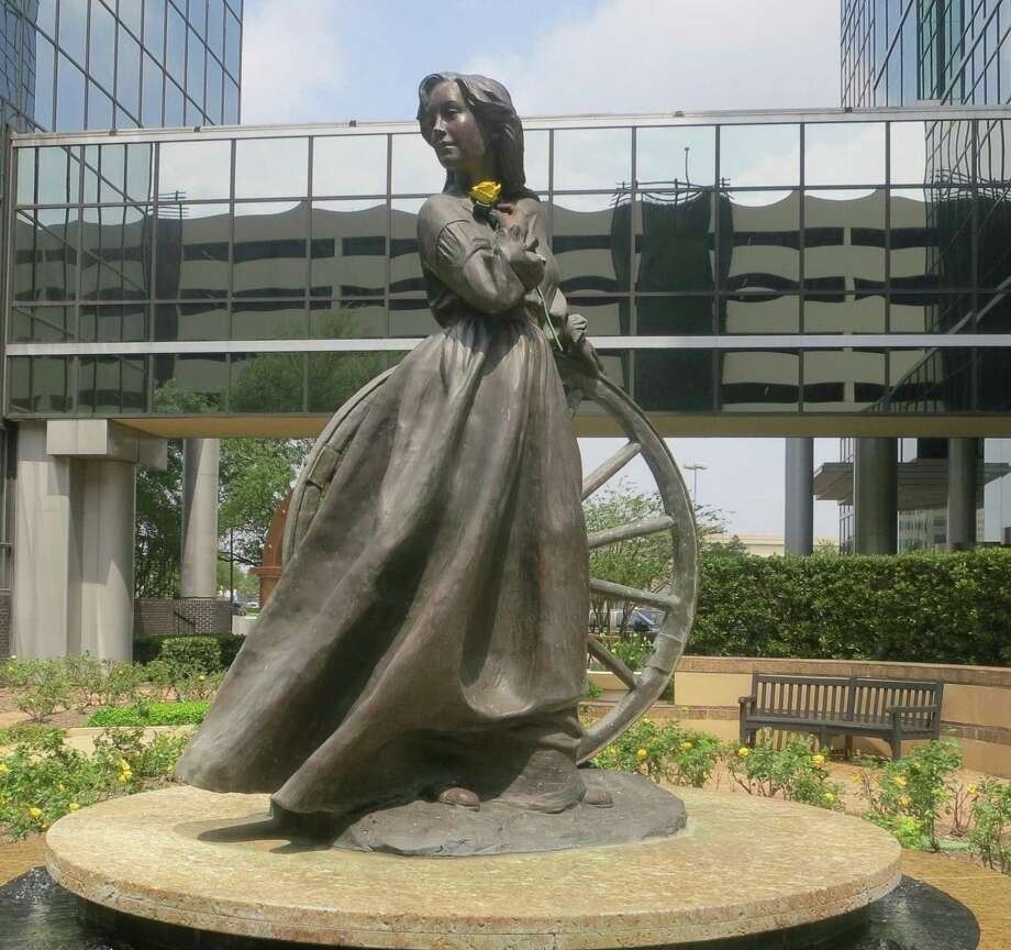 A statue of Emily Morgan by Veryl Goodnight stands amid yellow roses at an office complex in Houston. Photo: Houston Chronicle File Photo / Houston Chronicle