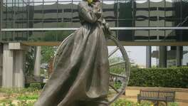 A statue of Emily Morgan by Veryl Goodnight stands amid yellow roses at an office complex in Houston.