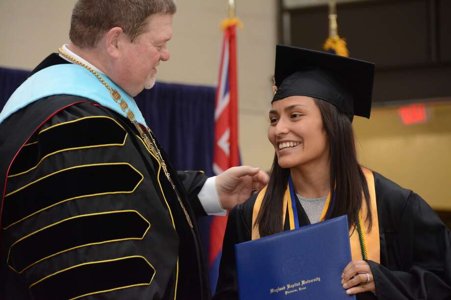 Wayland Baptist University graduating senior Mayra Ramirez of El Paso receives her diploma and congratulations from Wayland President Dr. Bobby Hall at graduation on Saturday afternoon. Ramirez, a member of the Pioneer wrestling team, served as the student speaker.
