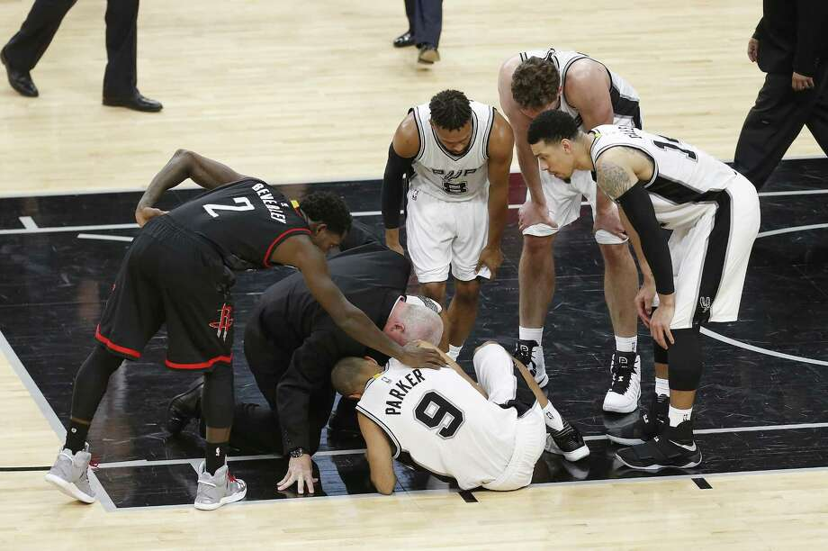 Spurs' Tony Parker (09) lays on the floor after an injury in the second half as teammates Patty Mills (08), Pau Gasol (16) and Danny Green (14) along with Houston Rockets' Patrick Beverley (02) and Spurs' Athletic Trainer Will Sevening check on him in Game 2 of the Western Conference semifinals at the AT&T Center on Wednesday, May 3, 2017. (Kin Man Hui/San Antonio Express-News) Photo: Kin Man Hui, Staff / San Antonio Express-News / ©2017 San Antonio Express-News
