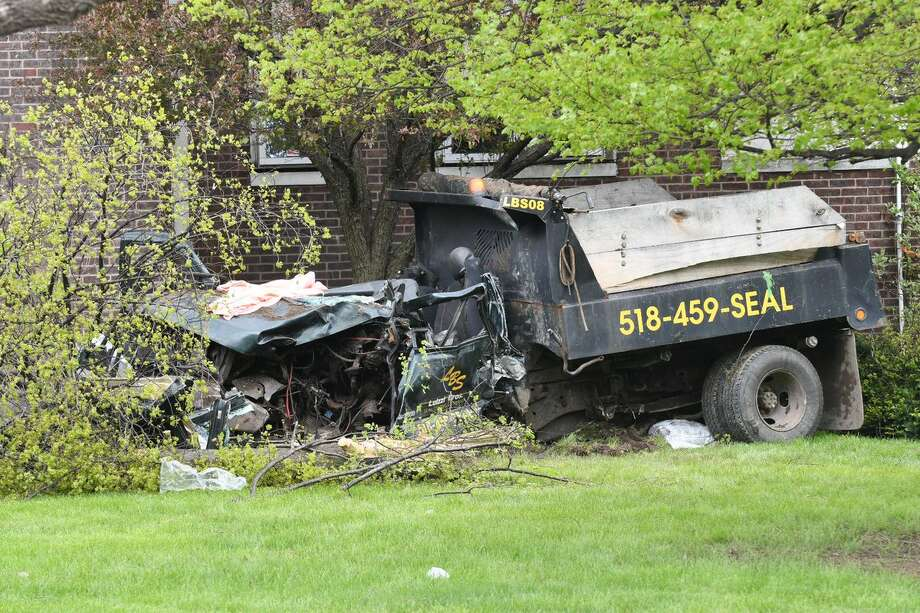 The driver was listed in critical condition after a dump truck slammed into a tree at the intersection of Broadway and Lawn Avenue in North Albany on Monday. Photo: Will Waldron / Times Union