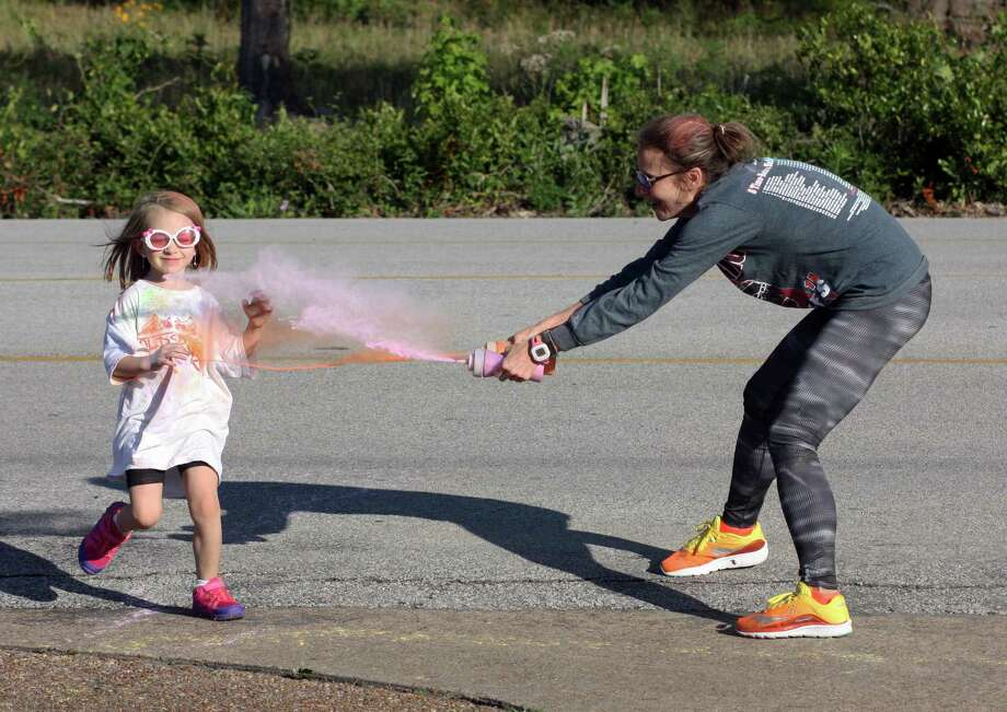 Laila Corbin gets dusted with pink and orange paint as she runs past Courtney Bailes at the Second Annual 5K Color Run at Street Elementary. Corbin has participated in both color runs with her grandmother, Susan Butler. Photo: Vanesa Brashier