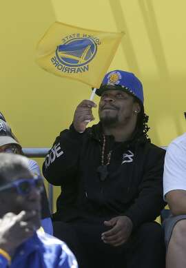 Seattle Seahawks running back Marshawn Lynch waves a Golden State Warriors flag during a rally for the Warriors winning the NBA championship in Oakland, Calif., Friday, June 19, 2015. (AP Photo/Jeff Chiu)