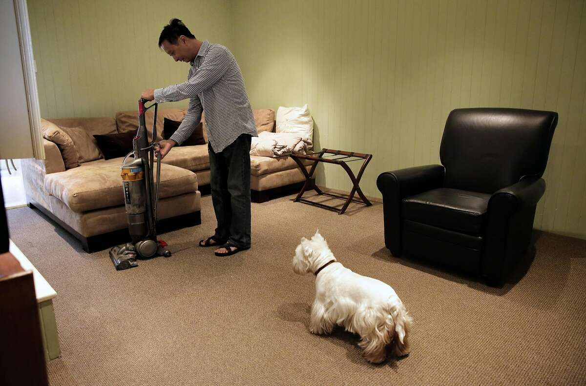 """Airbnb host Peter Kwan co-chairman of the Homesharers Democratic Club, with his dog, """"Haley"""" close by prepares his rental for the next guest at his home in North Beach neighborhood in San Francisco, Ca., on Monday May 8, 2017. Kwan has been registered with the city ever since it became possible."""