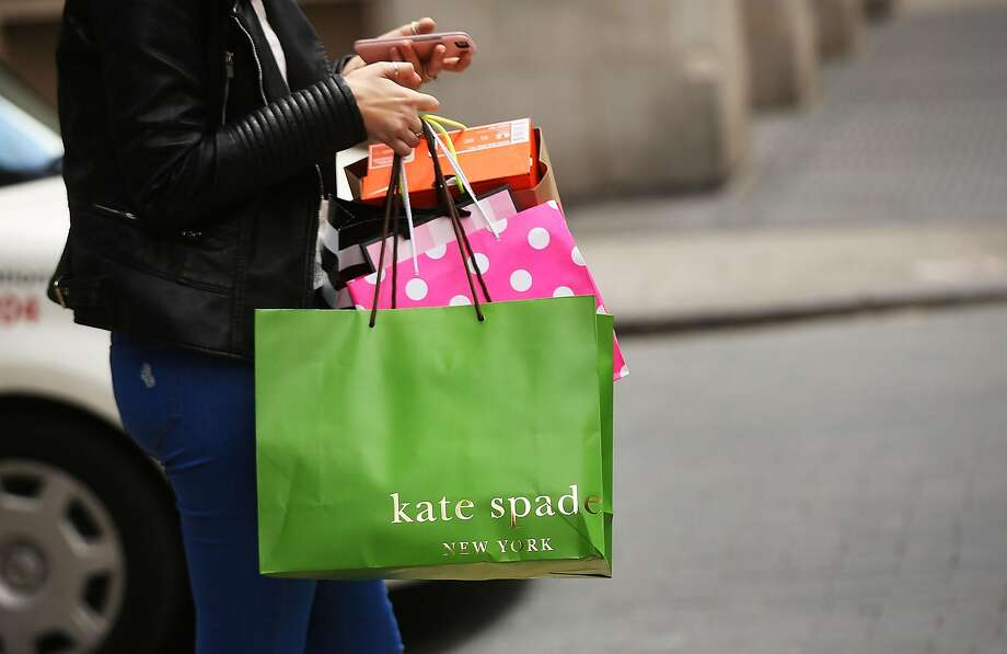 A woman walks out of a Kate Spade store in the SoHo neighborhood of Manhattan on May 8, 2017 in New York City. Coach, the American maker of high-end luxury goods, announced on Monday that it would buy rival Kate Spade in a $2.4 billion deal. Photo: Spencer Platt, Getty Images