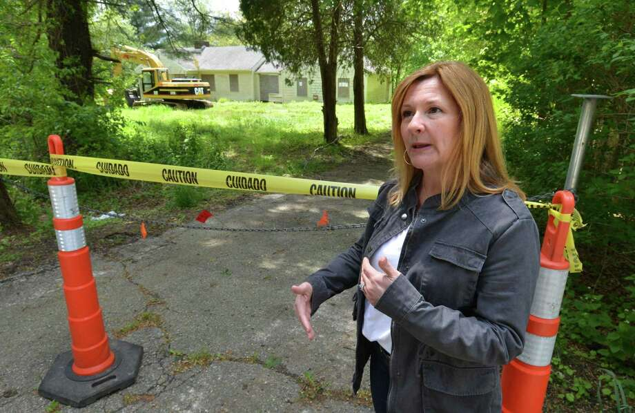 Kelly Danziger stands in front of the abandoned house and property at 283 Richards Ave. on Monday May 8, 2017 in Norwalk Conn. Kelly and her neighbors on the street have fought to have the house demolished under Norwalk's blight ordinance and will see the house torn down on Tuesday, after 9 years of legal issues Photo: Alex Von Kleydorff / Hearst Connecticut Media / Norwalk Hour