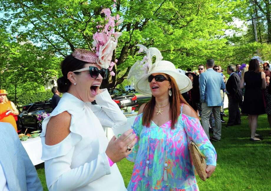 Fairfield resident Janet Megdadi, left, reacts to finding her next-door neighbor Marlowe Mitchell attending the Pequot Library's 8th annual Derby Day fundraiser. Photo: Christian Abraham / Hearst Connecticut Media / Connecticut Post