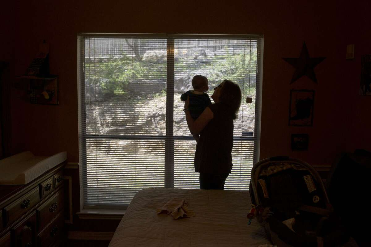 """Kathy Friend, a """"therapuetic foster parent,"""" holds an infant she is babysitting for another foster care family at her home in San Antonio."""