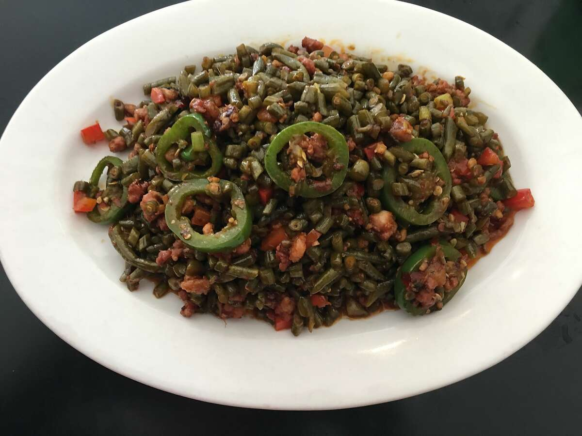 Stir-fried pickled long beans with ground pork and chiles was a staple dish for Lily Ji growing up near the Sichuan capital of Chengdu. The intensely spicy dish � heavy on the vegetables with the pork used as a garnish � made for a flavorful, yet economical meal for Ji's mother to feed her large family. It has since become a staple at Ji's Castro restaurant, Mama Ji�s.