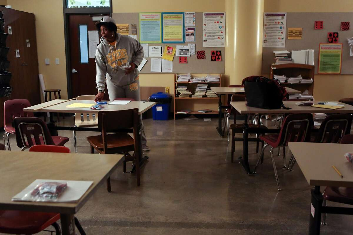 Math teacher and badminton coach Etoria Cheeks cleans up her classroom after finishing coaching during a badminton match at The Academy San Francisco high school on Tuesday, April 4, 2017 in San Francisco, Calif. It is not unusual for Cheeks to spend 12 hour days at the school.