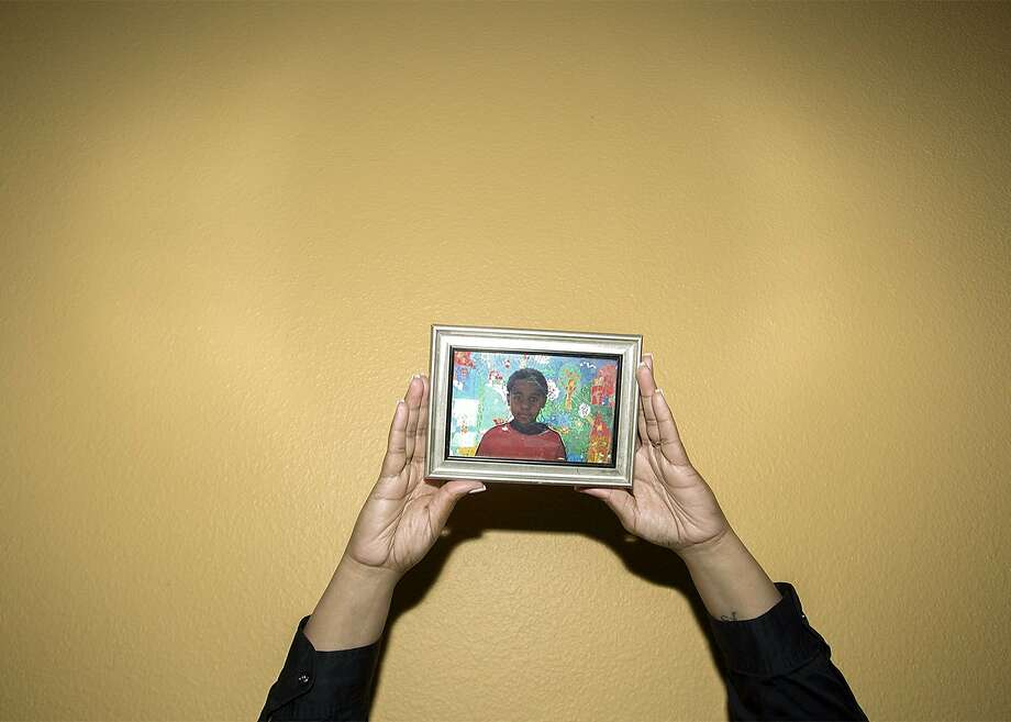 """One of the photos from Wesaam Al-Badry's """"Our Sons"""" series shows Pamela Saucier holding her son's first-grade photo. Her son, David, was slain in 2015. Photo: By Wesaam Al-Badry"""