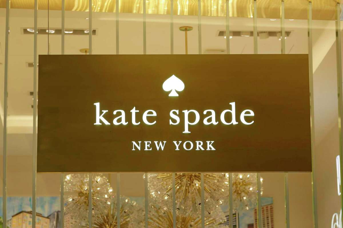 A Kate Spade sign hangs in the window of one of their shops, in New York, Monday, May 8, 2017. Coach will spend $2.4 billion for Kate Spade, tying together two premier brands in the luxury goods sector that have fought to snare younger shoppers. (AP Photo/Richard Drew) ORG XMIT: NYRD102