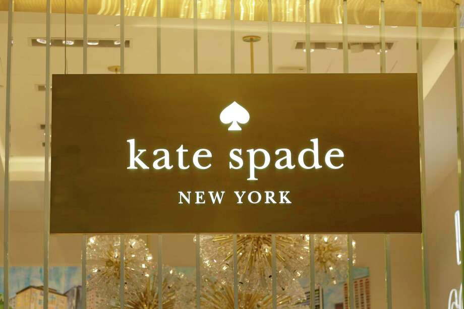 A Kate Spade sign hangs in the window of one of their shops, in New York, Monday, May 8, 2017. Coach will spend $2.4 billion for Kate Spade, tying together two premier brands in the luxury goods sector that have fought to snare younger shoppers. (AP Photo/Richard Drew) ORG XMIT: NYRD102 Photo: Richard Drew / AP