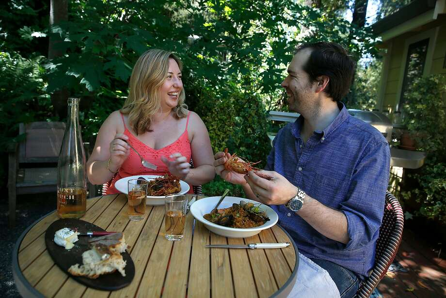 Perry Hoffman and Kristen Brott have paella on the patio of their Healdsburg cottage. Photo: Liz Hafalia, The Chronicle