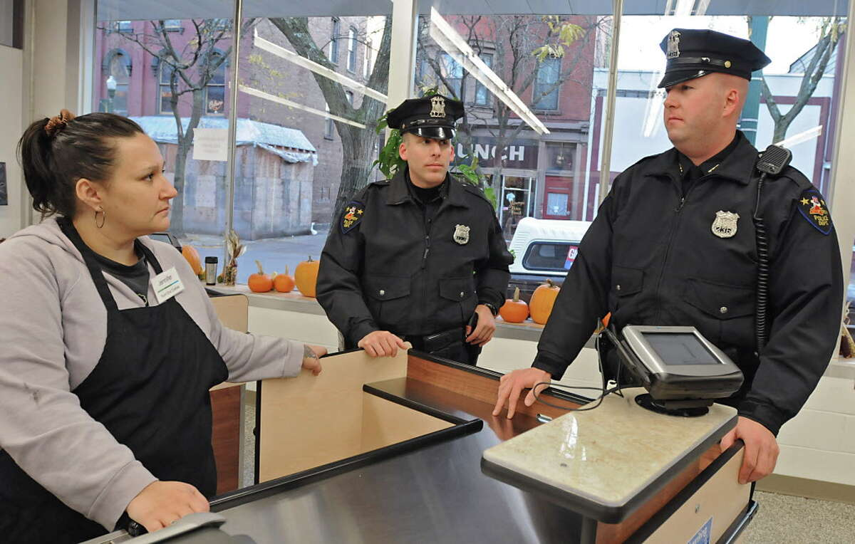 Troy police officers Craig Faby, middle, and Shane Kiley talk to front end cashier Jennifer DeArmas in the Pioneer food co-op in Troy, NY on November 1, 2010. (Lori Van Buren / Times Union)