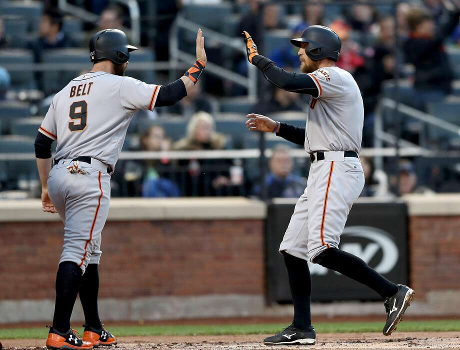Brandon Belt greets Hunter Pence at home plate after Pence's two-run homer gave the Giants a 2-0 lead in the first inning. Photo: Elsa, Getty Images