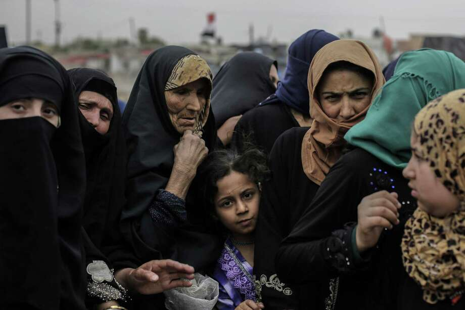 Residents wait at a food distribution point as Iraqi forces continue to make slow progress in the fight against ISIS in Mosul. Photo: Bram Janssen / Associated Press / AP