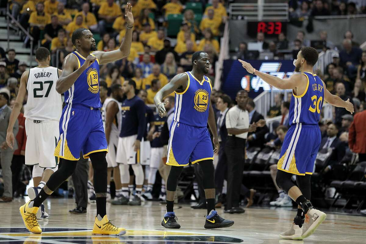 Kevin Durant (35), Draymond Green (23) and Stephen Curry (30) high five during a timeout in the second half as the Golden State Warriors played the Utah Jazz at Vivint Smart Home Arena in Salt Lake City, Utah, on Monday, May 8, 2017, in Game 4 of the 2017 Western Conference Semifinals. The Warriors defeated the Jazz 121-95 to sweep the series and advance to the Western Conference Finals