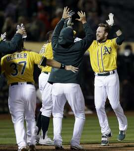 Oakland Athletics' Jed Lowrie, right, celebrates after hitting a walk off home run off Los Angeles Angels' Deolis Guerra in the eleventh inning of a baseball game Monday, May 8, 2017, in Oakland, Calif. (AP Photo/Ben Margot)