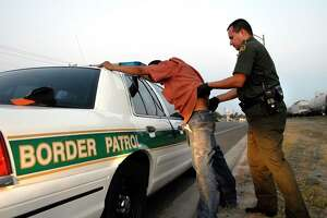 Border Patrol agent Eric Castillo searches a suspected illegal immigrant in Harlingen, Texas on June 27, 2006.  The man, reportedly from Honduras, was apprehended after being found hiding in a railroad car by Border Patrol agents and Union Pacific canine police .  Photographer: Eddie Seal/Bloomberg News