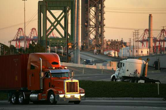 LONG BEACH, CA - JULY 06: Trucks carry shipping containers at the ports of Long Beach and Los Angeles on July 6, 2006 in Long Beach, California. In the Los Angeles area, studies indicate that diesel exhaust from trucks, locomotives, heavy equipment and ships causes cancer and is responsible for 70% of pollution-related health problems and hundreds of deaths every year. Rather than wait for the international agency that regulates the global shipping industry, the International Maritime Organization, to implement considered changes to strengthen emissions standards for cargo vessels, the ports recently unveiled an ambitious clean-air plan that could significantly improve air quality. The proposal seeks to reduce diesel emissions from cargo ships, trains and trucks by more than 50% over a five-year period at a cost of $2-billion.Almost 5,800 ships called at the ports of Los Angeles and Long Beach in 2005 released about 14,000 tons of air pollutants. Many ships emit as much exhaust per day as 12,000 cars. (Photo by David McNew/Getty Images)