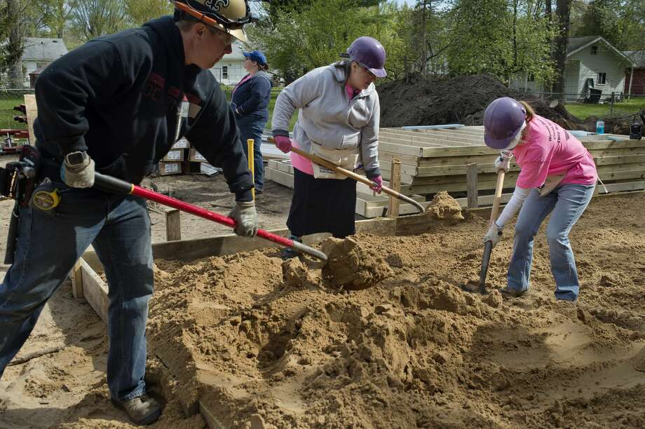 From left: Valley Electric employee Becky Manson, Senior Services employees Emily Eastman and Michelle Lather level sand on the soon to be garage floor during Habitat for Humanity's 10th annual National Women Build Week Tuesday morning. Photo: Brittney Lohmiller/Midland Daily News/Brittney Lohmiller