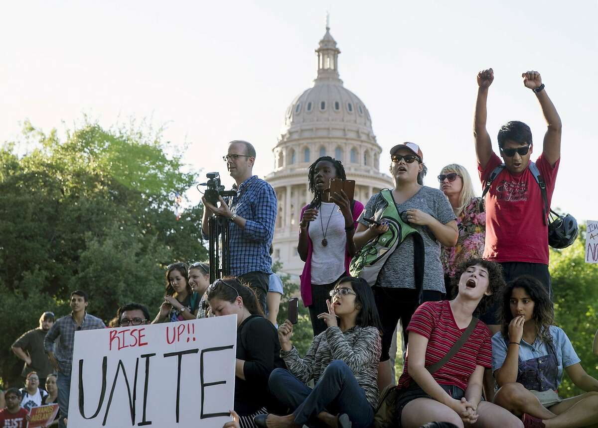 FILE - In this May 1, 2017, file photo, protesters against the Senate Bill 4 sanctuary cities ban rally outside the Texas Department of Insurance building where Republican Gov. Greg Abbott has an office in Austin, Texas. The Texas Legislature on Wednesday, May 3 passed a ban on so-called
