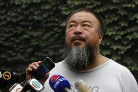 Dissident artist Ai Weiwei listens as his lawyer announces over a speakerphone the verdict of Ai's lawsuit against the Beijing tax authorities in Beijing Friday, July 20, 2012. A Beijing court on Friday rejected an appeal by Ai against a more than $2 million fine for tax evasion, which he says is part of an intimidation campaign to stop him from criticizing the government. (AP Photo/Ng Han Guan)
