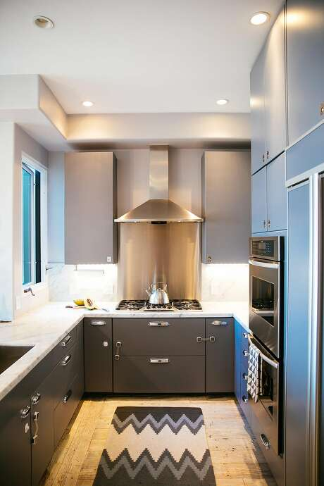"The kitchen: Benni Amadi spray-painted the kitchen cabinets matte gray and added small chrome ring pulls that are actually for boats: ""The hardware is a small reminder of home,"" says Amadi, from the port town of Genoa in Italy. Photo: Mason Trinca, Special To The Chronicle"
