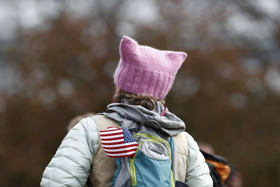 A protester wears a pink stocking hat while carrying an American flag on her pack during a march for science April 22 in Denver. Photo: David Zalubowski, Associated Press