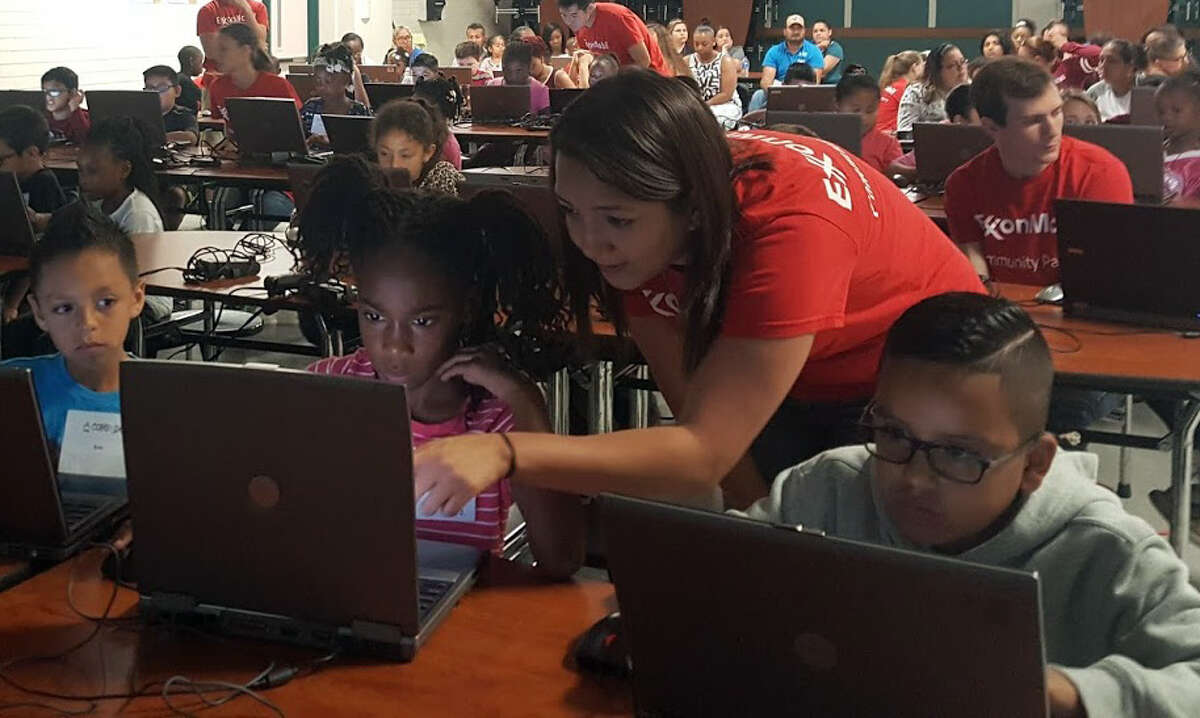 An ExxonMobil volunteer guides an elementary school student through computer training during the Comp-U-DoptComputer Adoption Program event at Lakeland Elementary School Saturday, May 6.