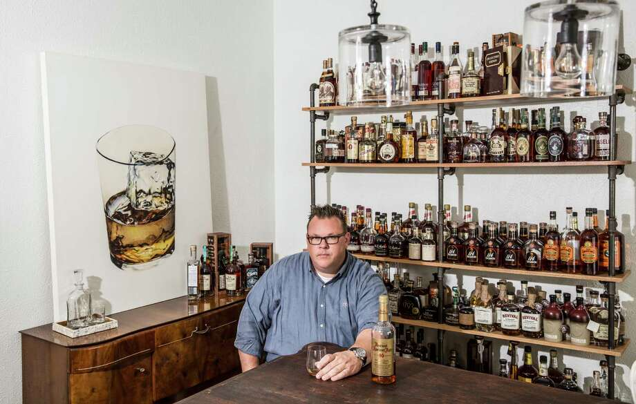 Chris Shepherd at home in Montrose, surrounded by his whiskey collection. Photo: Julie Soefer